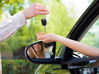 close up of female with arm outstretched taking car keys from man. Copy space